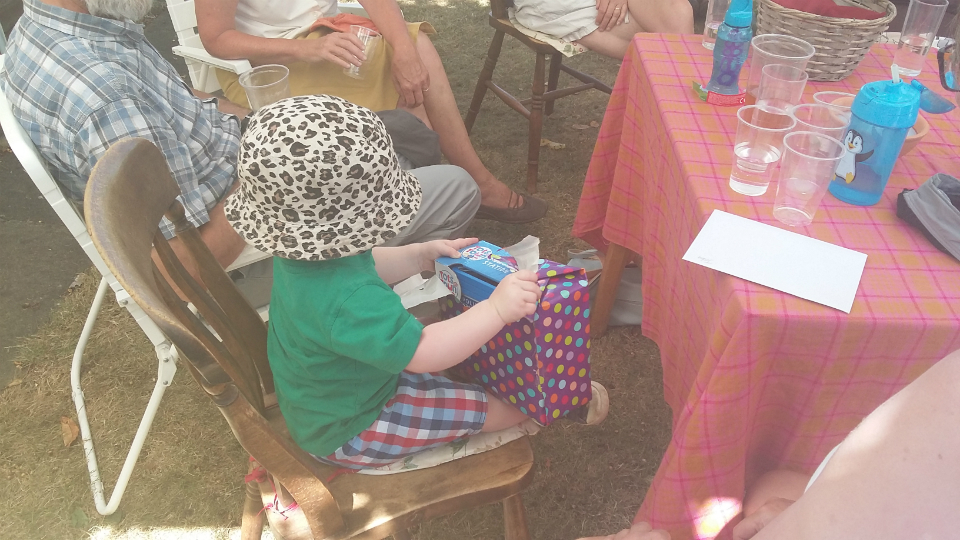 Joshua opening a birthday present at the Offton BBQ.