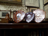 Trophies at St Mary-le-Tower. From l to r; the Cecil Pipe Memorial Bell (for the SE District Method Six-Bell Competition), the David Barnard Memorial Trophy (for the SE District Call-Change Six-Bell), George W Pipe Trophy (for the Essex and Suffolk Twelve-Bell Competition) and the Mitson Shield (for last year's Guild Six-Bell).